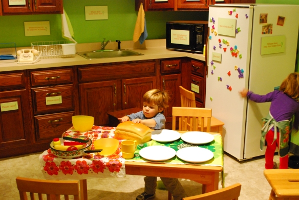 One little boy sets the table, while another apron-clad visitor does some cleaning in the corner of our modern kitchen space.