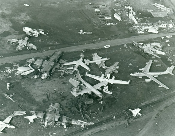 An aerial view following the October 1979 tornado shows the remains of many of the museum's aircraft. The Globemaster has been sheared into large pieces (the wing section is lying inverted at bottom center of photo) while the Flying Boxcar's fuselage lies bisected with its wings ripped off (top center of photo). The S-59 helicopter survived and remains part of the New England Air Museum collection. CHS 2007.35.13