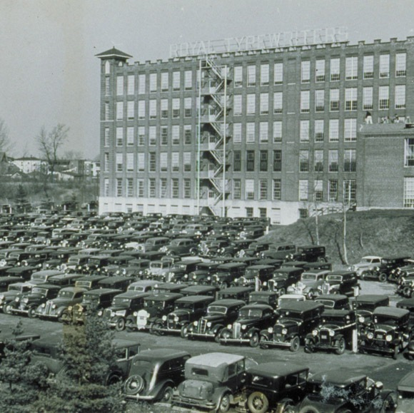 "Royal Typewriter Company with automobiles parked in front, New Park Avenue, Hartford, 1930s. Photographic print by James Parker, Connecticut Historical Society collection. Note the rooftop letters atop the building, which read: ""ROYAL TYPEWRITERS""."